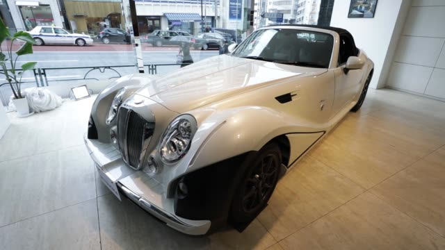 Pedestrians walks past a Mitsuoka Motor Co showroom in Tokyo Japan on Thursday Feb 22 The redesigned Mitsuoka Motor Co Himiko convertible vehicle...