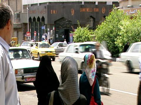 vidéos et rushes de pedestrians watch traffic as they wait to cross the busy street / tehran, iran - format vignette