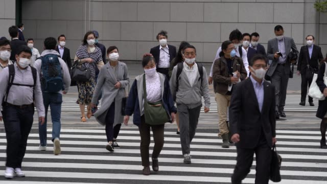 pedestrians wearing face masks walk past commercial buildings in the central business district on may 22, 2020 in tokyo, japan. - japan stock videos & royalty-free footage