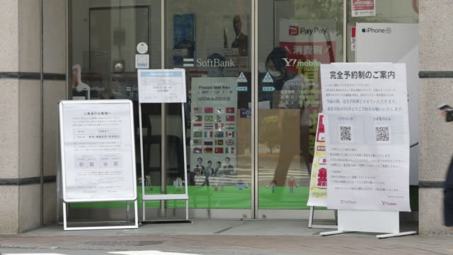 pedestrians wearing protective masks walk past a softbank corp store in tokyo japan on friday may 15 2020 softbank group corp expects to book a... - japan bloomberg stock videos & royalty-free footage