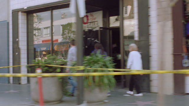 vidéos et rushes de pedestrians window shop near police tape on hollywood boulevard near wilcox avenue in los angeles. - hollywood boulevard
