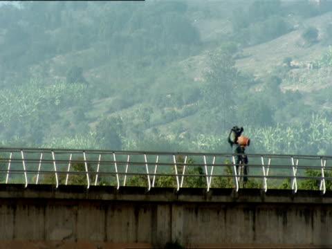 ms pedestrians with bundles on their heads and traffic crossing bridge / kigali, rwanda - gemeinsam gehen stock-videos und b-roll-filmmaterial