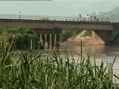 ws pedestrians with bundles walking across bridge over ruganwa river / kigali, rwanda - キガリ点の映像素材/bロール