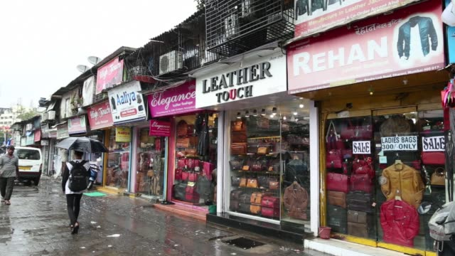 vídeos y material grabado en eventos de stock de pedestrians with umbrellas walk past leather goods stores in the dharavi area of mumbai, india, on tuesday, july 18 a customer enters a leather goods... - iva