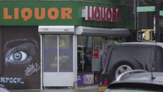 pedestrians with umbrellas walk past nondescript liquor store in brooklyn, new york. - beliebiger ort stock-videos und b-roll-filmmaterial