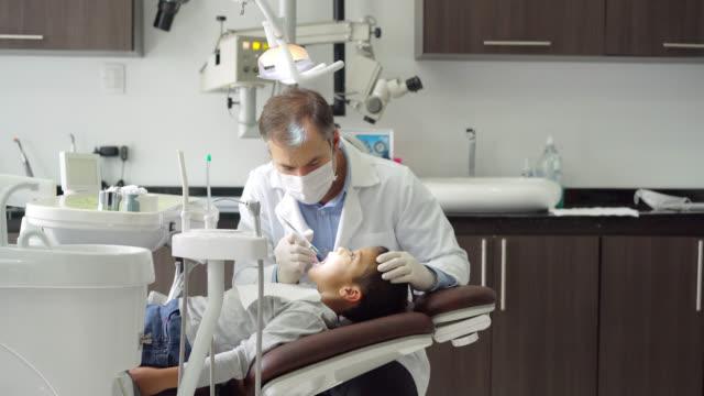 vídeos de stock, filmes e b-roll de odontólogo pediátrico, verificando os dentes de pacientes pequeno - pediatra