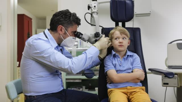 pediatrician examine boy's ear - childhood stock videos & royalty-free footage