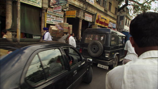 A pedicab driver moves through a busy street in New Delhi. Available in HD.