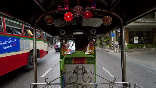A pedicab driver moves through traffic in downtown Bangkok.