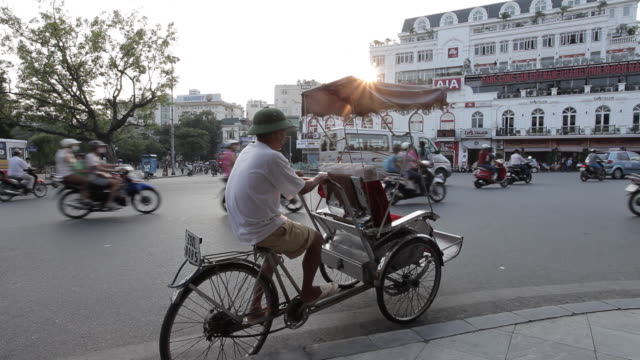 A pedicab driver watches as traffic passes on a busy Hanoi street.