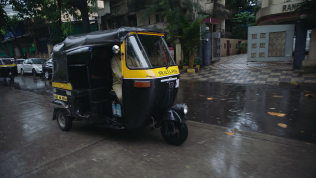 SLO MO. Pedicab drives past and passenger sticks tongue out at camera on rainy Mumbai street.