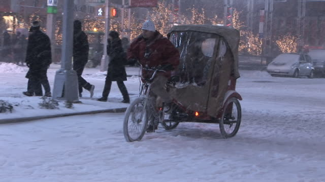Pedicab travelling through snow covered streets of New York Available in HD