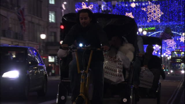 vídeos de stock, filmes e b-roll de pedicabs carry passengers through regent street in london during the christmas holiday. - jinriquixá puxado por bicicleta