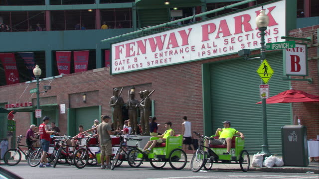 ws pedicabs in front of 'the teammates' statue featuring bobby doerr, dom dimaggio, johnny pesky and ted williams at fenway park gate b / boston, massachusetts, usa - scrittura occidentale video stock e b–roll