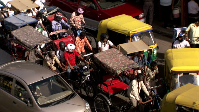 vídeos de stock, filmes e b-roll de pedicabs, pedestrians, and other motorists create a traffic jam in delhi, india. - jinriquixá puxado por bicicleta