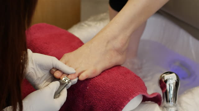 Pedicurist practicing foot care cleaning toenail