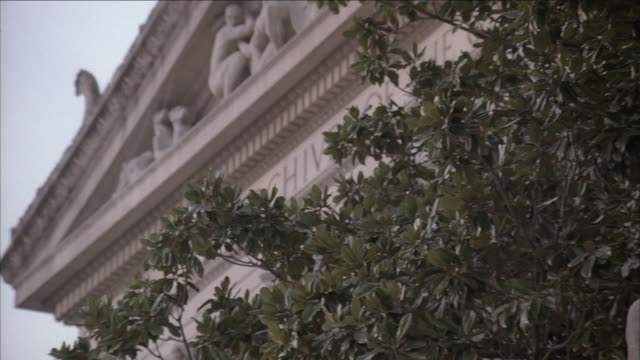 stockvideo's en b-roll-footage met pan pediment on front of national archives building partly obscured by leafy tree, and statue of heritage by james earl fraser / washington, d.c., united states - national archives washington dc