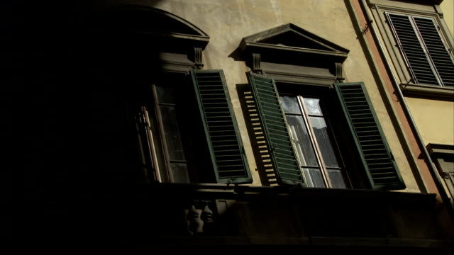 vidéos et rushes de pediments top windows with green shutters on an apartment building in florence, italy. available in hd. - fronton
