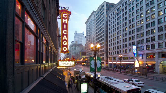 vidéos et rushes de t/l wa ha pedple and traffic passing the chicago theater downtown at dusk / chicago, illinois, usa - chicago illinois