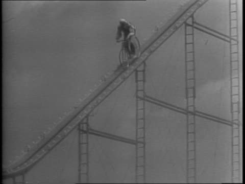 peejay ringens takes 200 ft plunges from bicycle into 3 foot tank of water / a 60 yearold stuntman waves to the crowd before ascending a ladder /... - anno 1943 video stock e b–roll