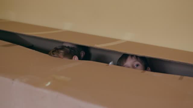 peeking from cardboard box, slow motion, handheld shot - hide and seek stock videos and b-roll footage