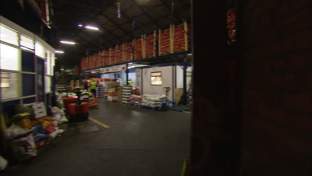 peeking inside a supermarket's stock room - halle gebäude stock-videos und b-roll-filmmaterial