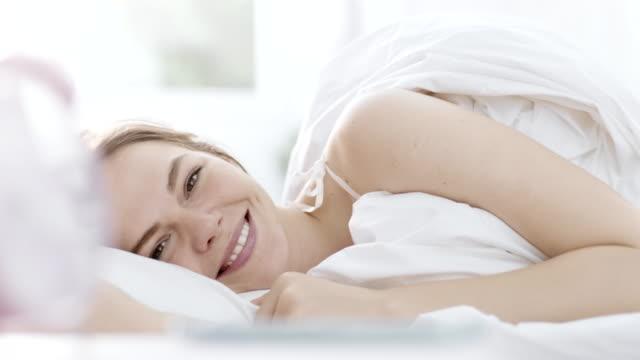 Spähen unter Bettdecke und lächelnd