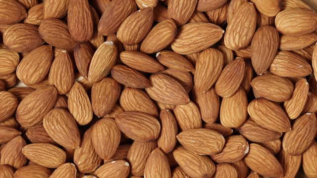 vidéos et rushes de les noix d'amandes pelées tournent dans le sens des aiguilles d'une montre, arrière-plan macro-alimentaire, vue de dessus - vitamine a