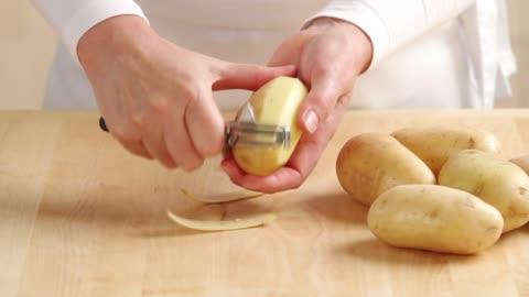stockvideo's en b-roll-footage met peeling a potato - pellen