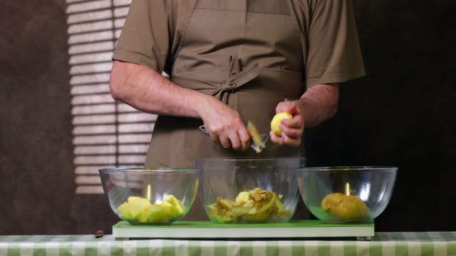 peeling and chopping potatoes. - only mature men stock videos & royalty-free footage