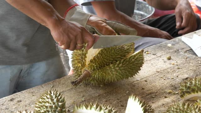stockvideo's en b-roll-footage met peeling durian met mes - gepunt