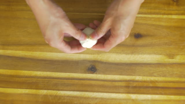 peeling garlic cloves on wooden cutting board - garlic stock videos & royalty-free footage