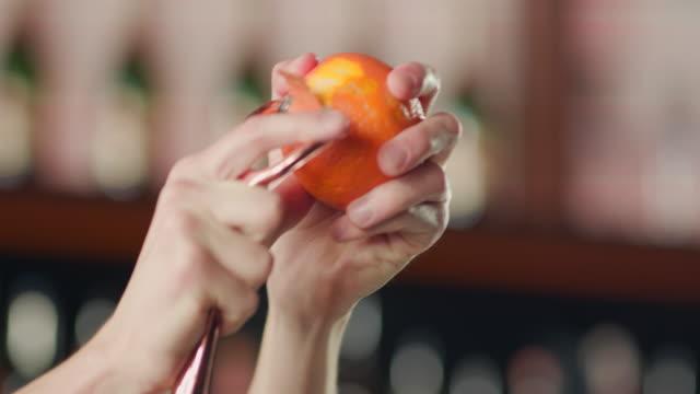 stockvideo's en b-roll-footage met peeling oranje met een dunschiller - schil