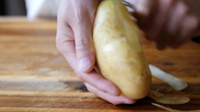 peeling potatoes - raw potato stock videos & royalty-free footage