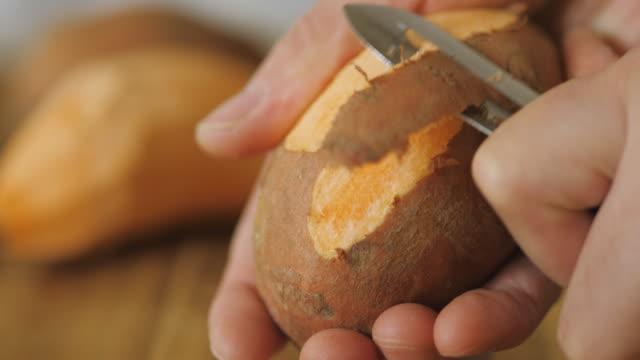 stockvideo's en b-roll-footage met het schillen van zoete aardappel - schil