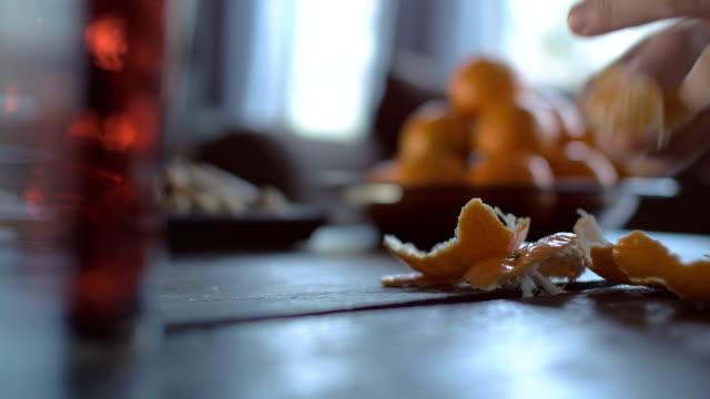 vídeos de stock, filmes e b-roll de descascar as tangerinas em mesa de madeira - casca de fruta