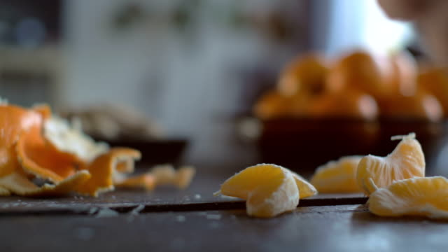 Peeling Tangerines on Wooden Table