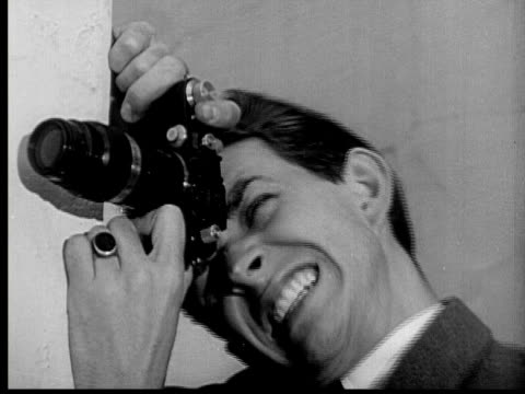 stockvideo's en b-roll-footage met 1937 b/w cu peeping tom (hal richardson) making weird faces as he takes photos while hiding around corner - tanden op elkaar klemmen