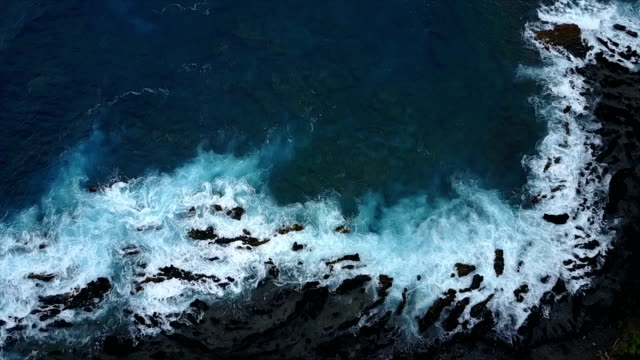 peering down at rough waters breaking over rocks on shore - gray color stock videos & royalty-free footage