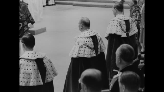 peers in coronation attire / altar showing regalia / queen elizabeth ii enters with maids of honor and approaches the archbishop of canterbury /... - coronation of queen elizabeth ii stock videos and b-roll footage
