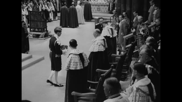 peers in coronation attire / queen elizabeth ii enters the coronation theater with maids of honor / archbishop of canterbury geoffrey fisher bows in... - coronation stock videos and b-roll footage