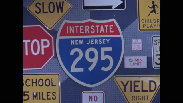 peg board display of bright road signs zoom out from new jersey i-295 sign to stop sign and others - road sign stock videos & royalty-free footage