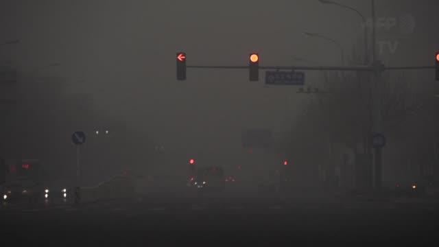 pekin estaba el martes en alerta naranja por tercer día consecutivo debido a una contaminacion record en el norte de china recubierto de una niebla... - día stock videos & royalty-free footage