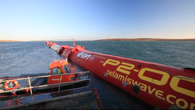 a pelamis p2 wave energy generator on the dockside at lyness on hoy, orkney isles, scotland, uk. the orkney's have huge potential for wave and tidal energy generation and are world leaders in testing such devices. the pelamis p2 is 180 m long, weights 1300 - netzteil elektronisches bauteil stock-videos und b-roll-filmmaterial