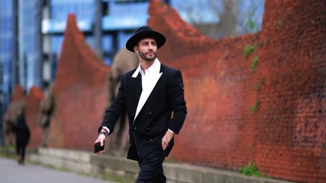 vídeos y material grabado en eventos de stock de pelayo diaz wears a black hat, a white shirt, a black blazer jacket with a white lapel and buttons, black pants, pointy leather boots, outside... - camisa blanca