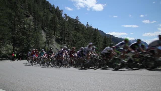 pan ws peloton climbing col de montgenevre, briancon - ツール・ド・フランス点の映像素材/bロール