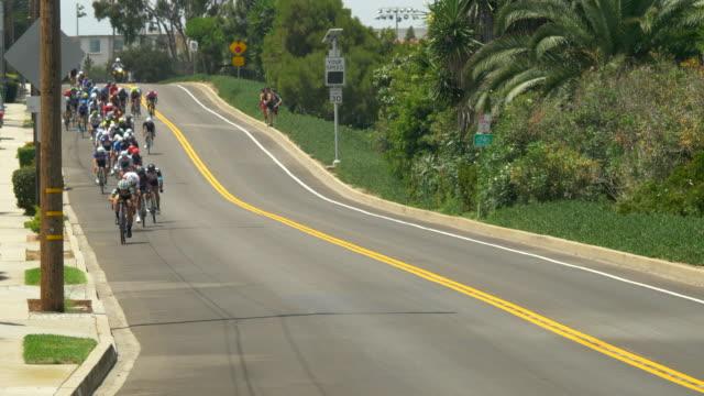 peloton group of men racing in a road bike bicycle race. - slow motion - プロトン点の映像素材/bロール
