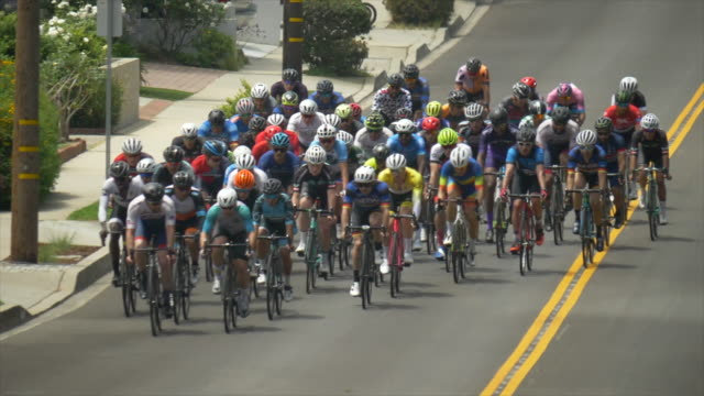 peloton group of men racing in a road bike bicycle race. - slow motion - ロードサイクリング点の映像素材/bロール