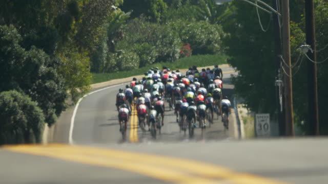 Peloton group of men racing in a road bike bicycle race.