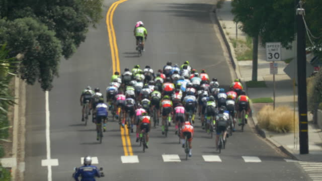 peloton group of men racing up a hill in a road bike bicycle race. - slow motion - プロトン点の映像素材/bロール